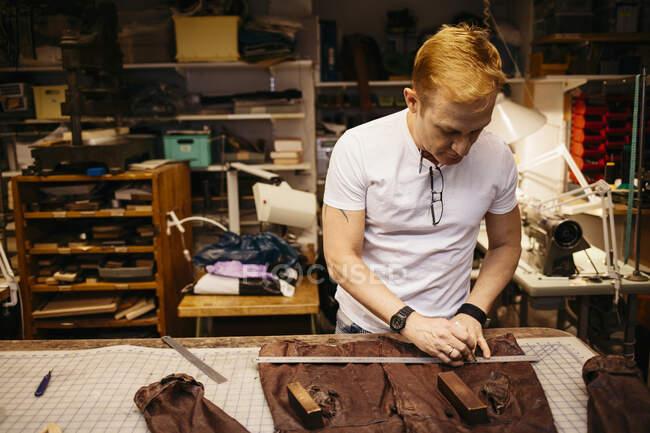 Homem maduro focado trabalhando em oficina de couro — Fotografia de Stock