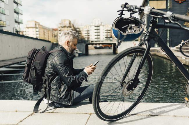 Un homme sur un téléphone intelligent avec une bicyclette à Stockholm, Suède — Photo de stock