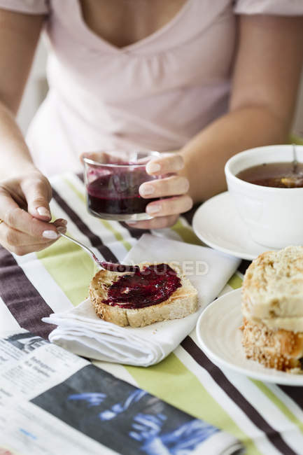 Cropped view of woman spreading jam on toast, selective focus — Photo de stock