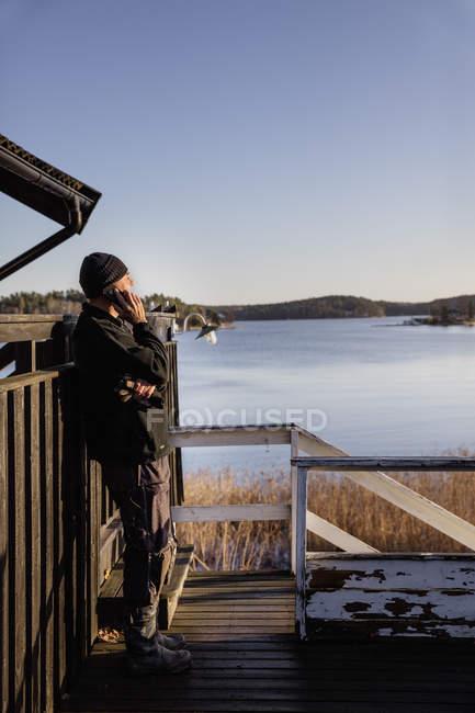 Людина притулившись паркан і розмовляти по телефону — стокове фото