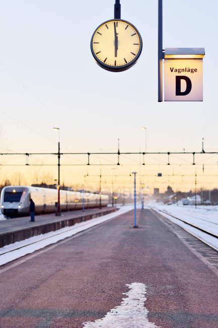 Reloj en la plataforma de la estación de tren, se centran en primer plano - foto de stock