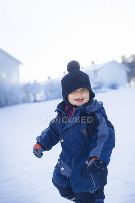 Young boy in warm clothing standing on snow — Stock Photo