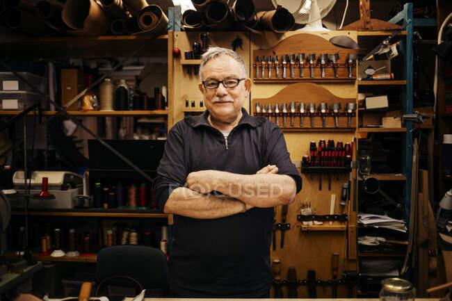Пенсионер в очках, работающий в кожевенной мастерской — стоковое фото