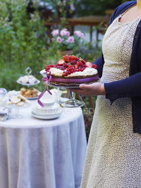 Женщина, несущая торт со свежими ягодами — стоковое фото
