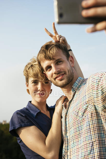 Joven pareja abrazándose y tomando selfie con smartphone en azotea de ciudad - foto de stock