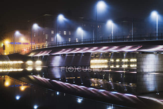 Illuminated bridge over river at night, northern europe — Stock Photo