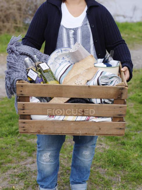 Mujer que lleva una gran caja de picnic de madera, se centran en primer plano - foto de stock