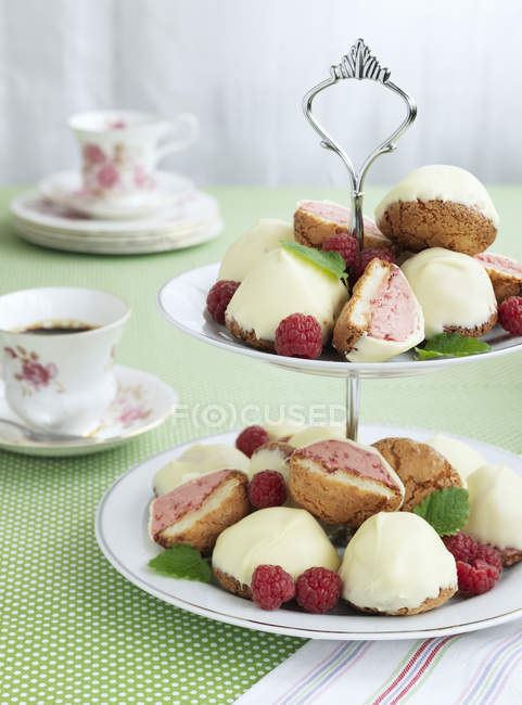 Raspberry cakes on cake stand, focus on foreground — Stock Photo