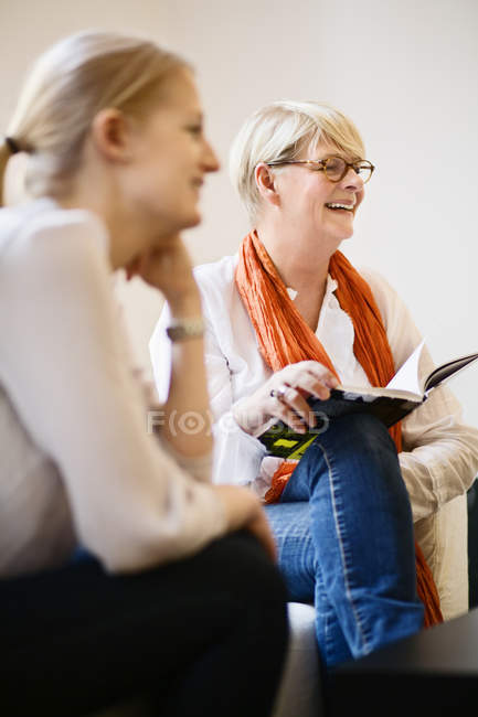 Smiling woman sitting and holding open book, differential focus — Stock Photo