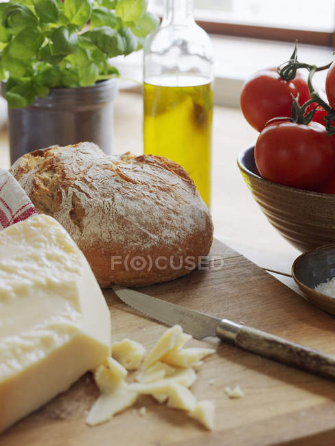Parmesan cheese and bread on cutting board — Stock Photo
