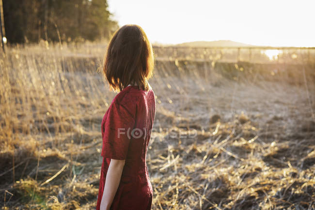 Young woman standing in field, focus on foreground — Stock Photo
