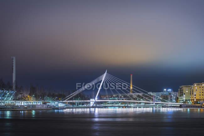 Night city scene with illuminated modern bridge — Stock Photo