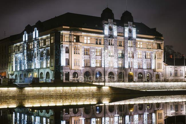 Illuminated buildings exterior at night, reflection at river — Stock Photo