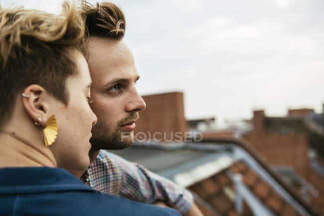 Giovane coppia fianco a fianco sul tetto contro cielo nuvoloso — Foto stock