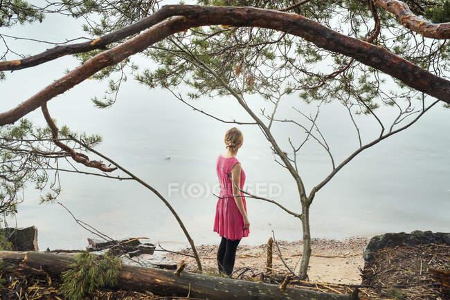 Mujer joven en vestido rosa mirando al mar - foto de stock