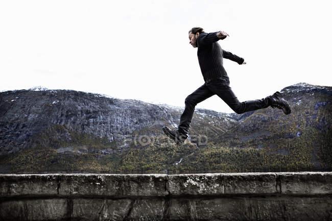 Homme sautant par-dessus le mur de Pierre — Photo de stock