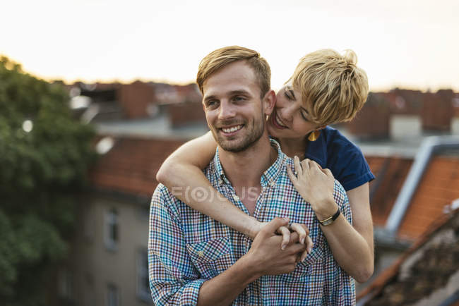 Young couple hugging on rooftop at sunset — Stock Photo