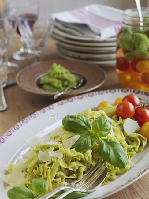Tagliatelle com pesto e queijo parmesão no prato — Fotografia de Stock
