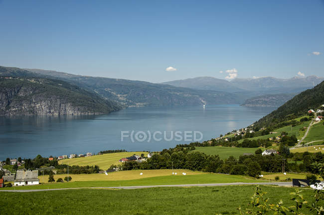 Village houses by lake in mountains, rural scene — Stock Photo