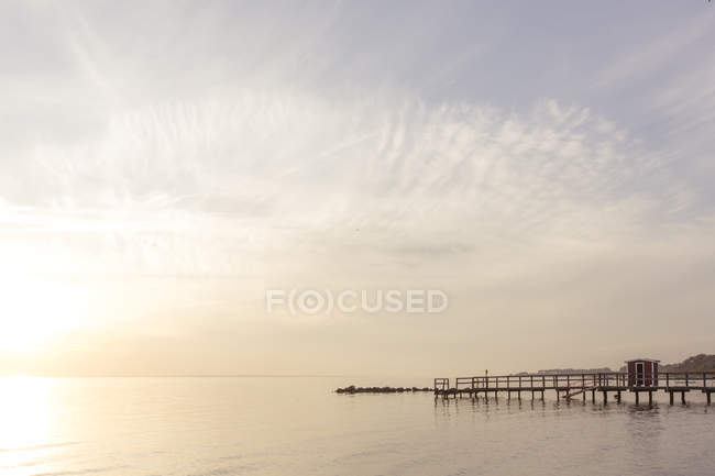 Seascape with jetty at sunset, tranquil scene — Stock Photo