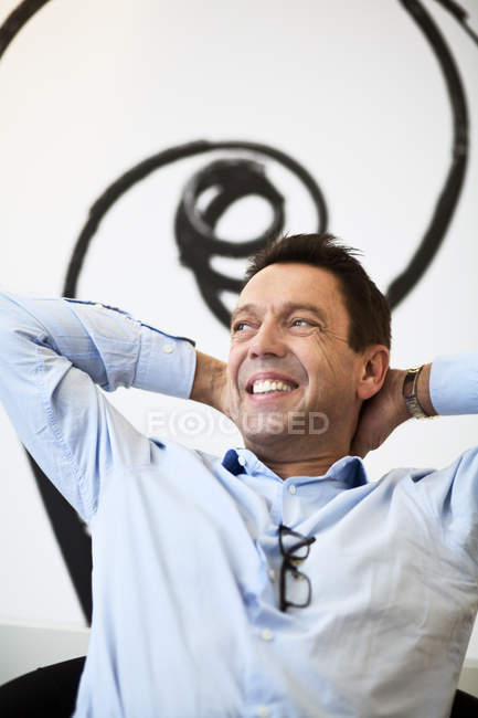 Smiling businessman sitting on chair and looking away — Stock Photo