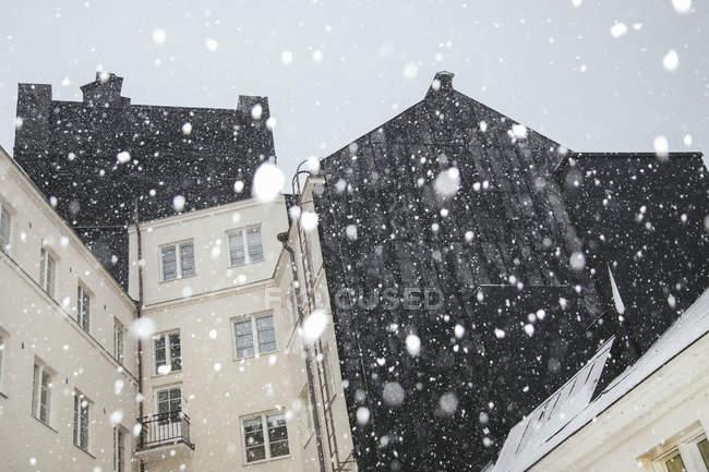 Снежинки против жилого здания, выборочный фокус — стоковое фото