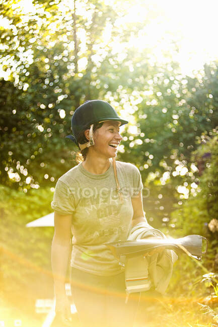 Woman laughing with horseriding boots and helmet — Stock Photo