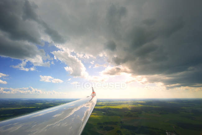 Крила літака з відображення хмарах зелений ландшафт — стокове фото
