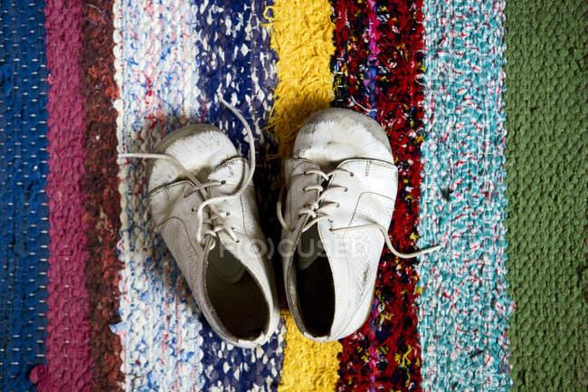 Vista de los zapatos de niño en alfombra colorida - foto de stock