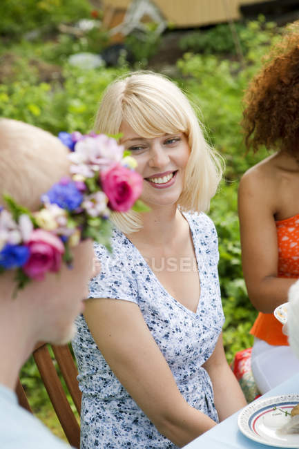 Young people sitting outside at picnic table — Stock Photo