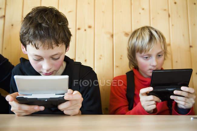 Zwei Teenager spielen Handheld-Spiel — Stockfoto