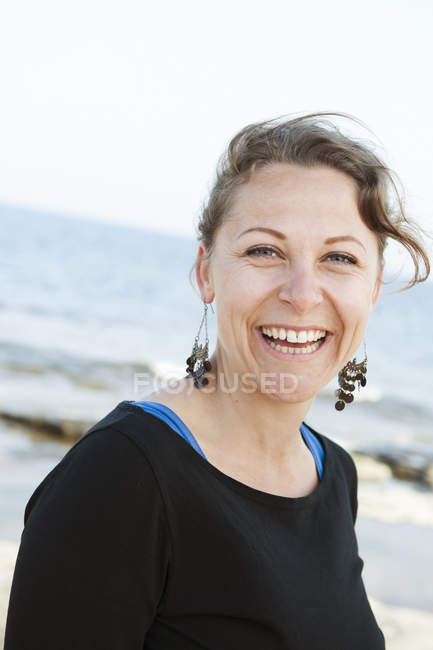 Portrait of smiling woman, sea in background — Stock Photo
