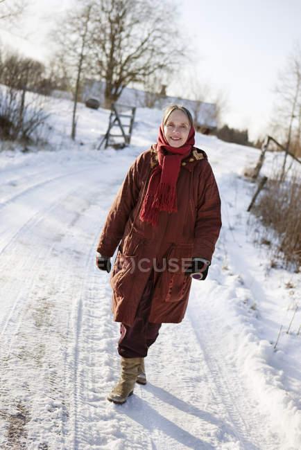 Senior woman walking along snow covered road — Stock Photo