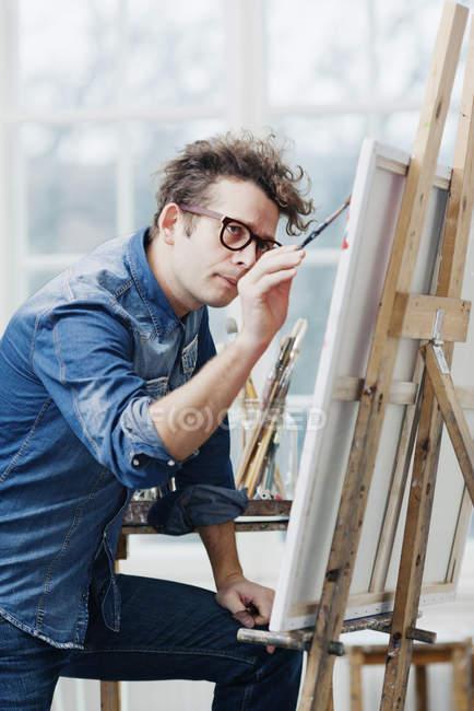 Mann mit Brille bemalt Staffelei — Stockfoto