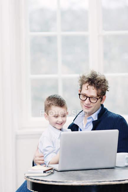 Père et fils portant une tenue formelle à l'aide d'un ordinateur portable et souriant — Photo de stock