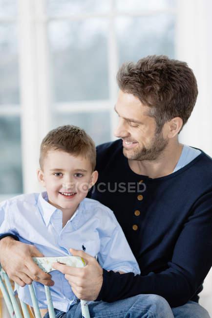 Padre e hijo sentados juntos y sonriendo - foto de stock