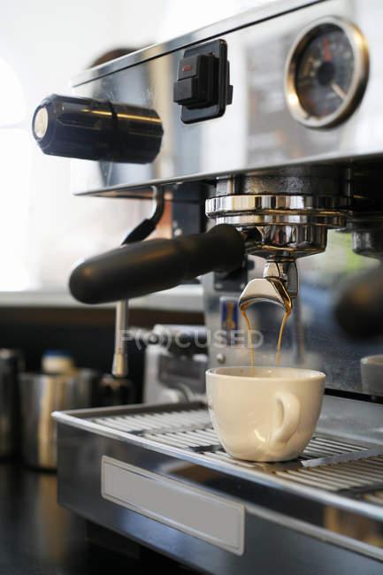 Espresso machine pouring coffee in white cup — Stock Photo