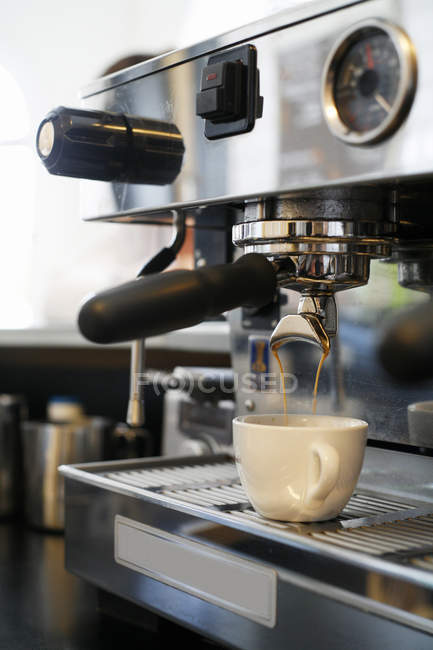 Espresso machine pouring coffee in white cup — Stock Photo