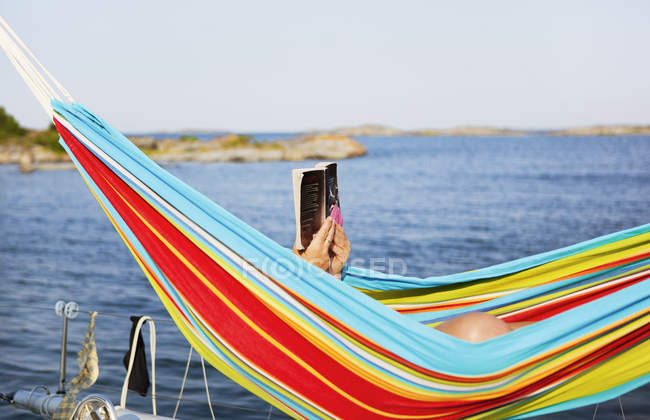 Man lying in hammock and reading book, selective focus — Stock Photo