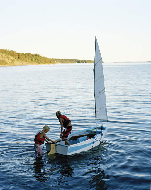 Two boys on sailboat on lake, selective focus — Stock Photo