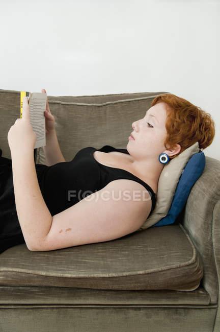 Junge Frau liegt auf Sofa und liest — Stockfoto