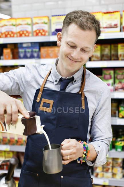 Barista pouring milk into jug, selective focus — Stock Photo