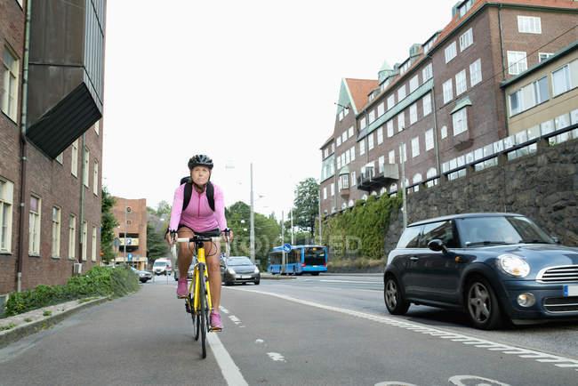 Femme mûre en vélo le long de la rue — Photo de stock