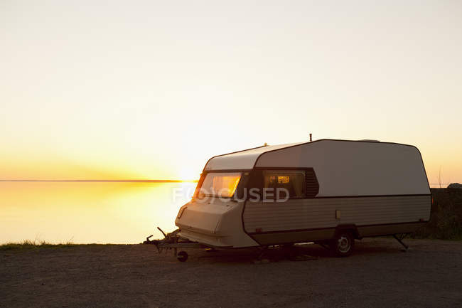 Camping trailer parked by lake at sunset — Stock Photo
