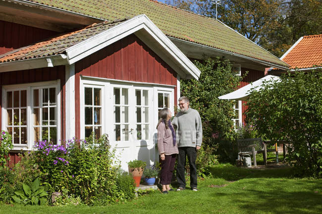 Man and woman standing outside house — Stock Photo
