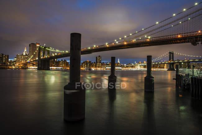 Puente iluminado y rascacielos en Nueva York al atardecer - foto de stock