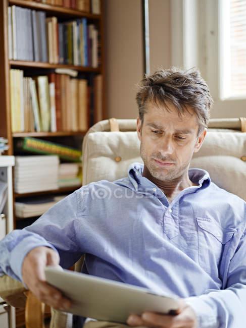 Uomo utilizzando tablet pc mentre seduto sulla poltrona — Foto stock