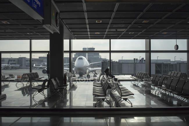 Terminal do aeroporto com avião em segundo plano — Fotografia de Stock