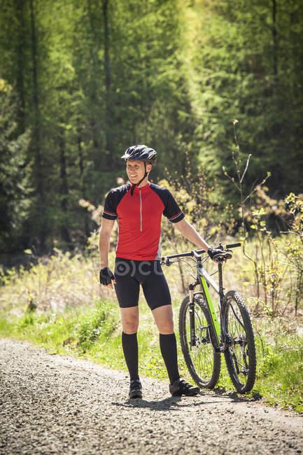 Человек, стоящий на горном велосипеде, сосредоточьтесь на переднем плане — стоковое фото