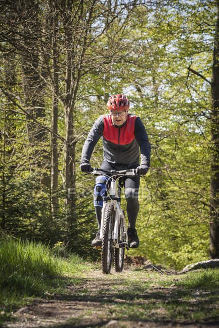 Зрелый человек едет на горном велосипеде через лес — стоковое фото